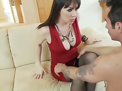 Hot and breasty darksome haired milf in sexy red dress RayVeness gets her shaved taco licked on the couch in her living room by a excited young darksome haired dude Joey Brass and enjoys