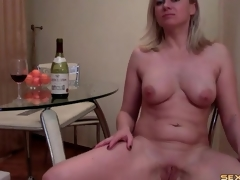 Curvy web camera angel blows a wine bottle and strips